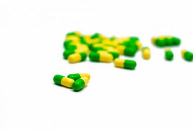 Green, yellow tramadol capsule pills on blurred capsule pills background with copy space. Cancer pain management. Opioid analgesics. Drug abuse in teenage.