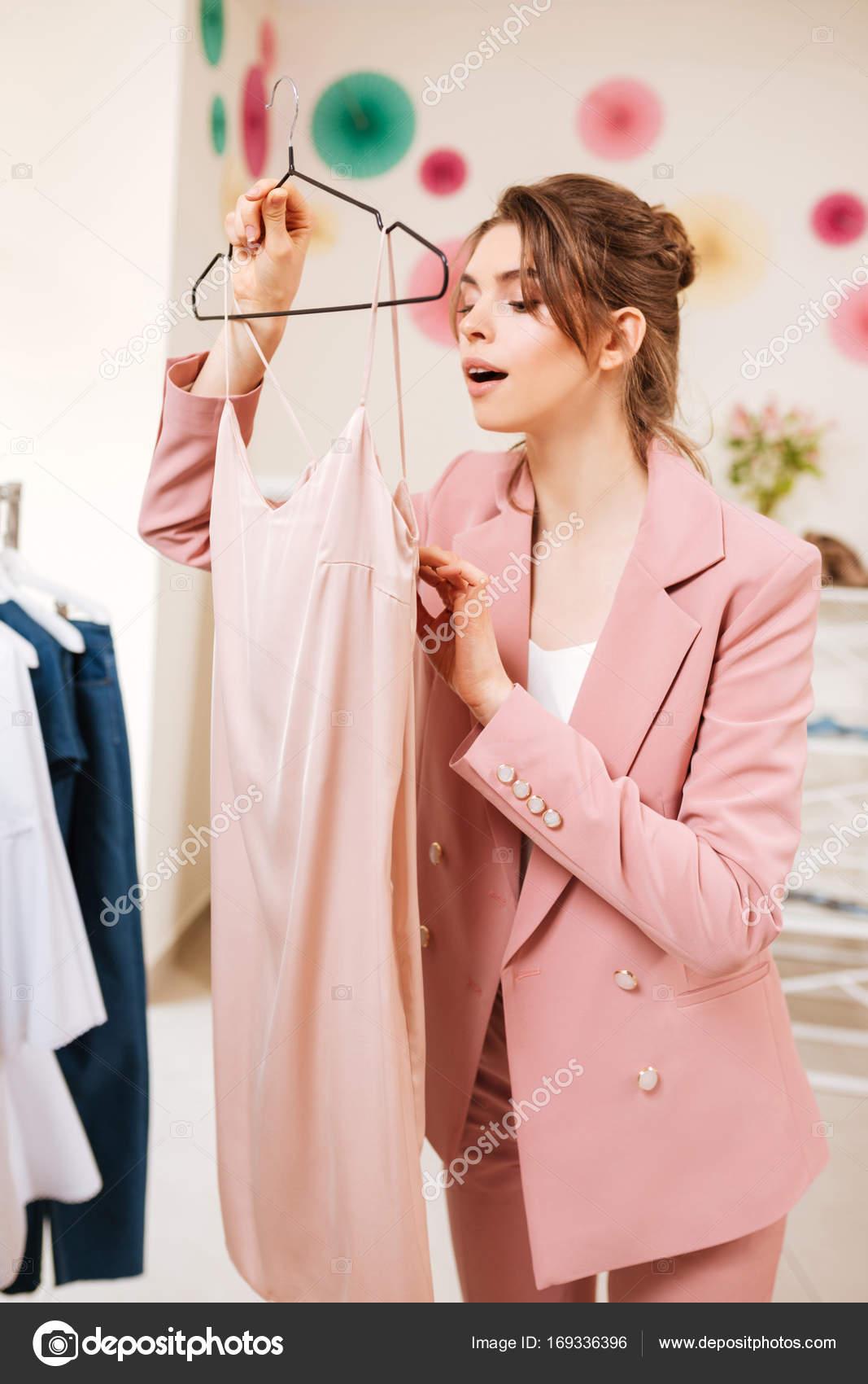 Bastante joven en traje pantalón rosa tiene compras en la boutique ...
