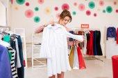 Fényképek Fiatal lány rózsaszín pantsuit a színes bevásárló szatyrok kezében kiválasztja ruhákat, divat butik