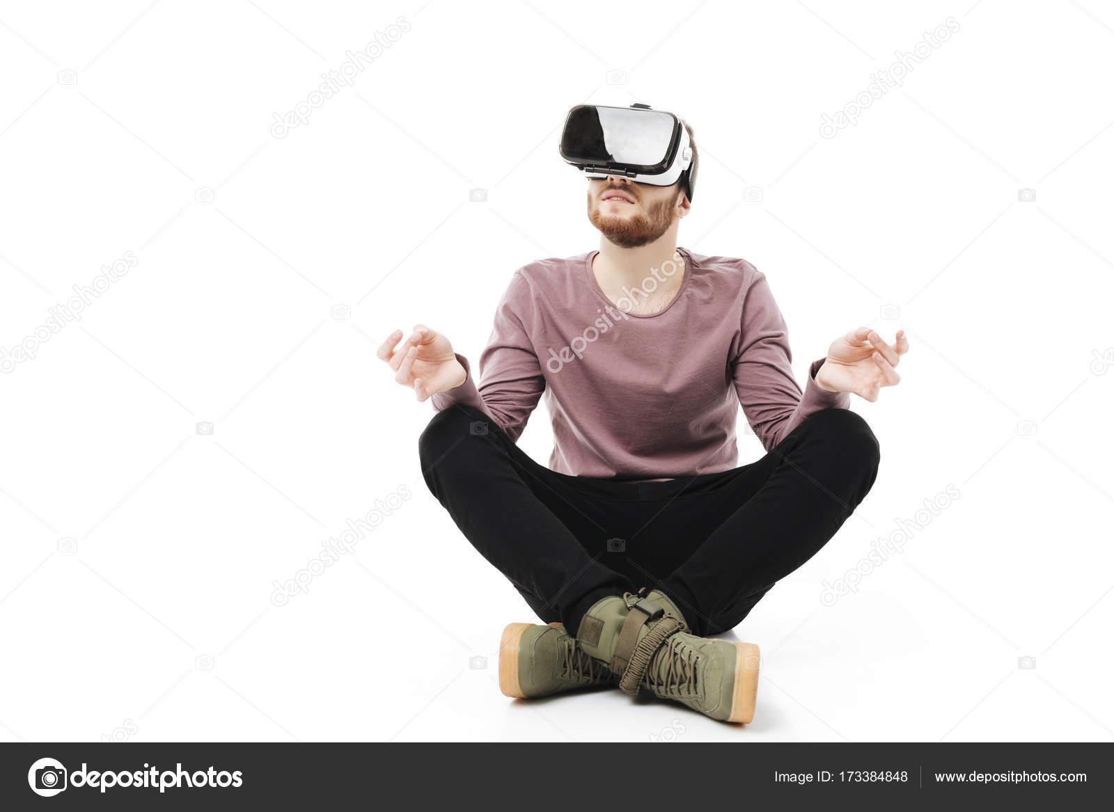 3691fb12f707b0 Jeune homme assis dans le studio et méditer tout en utilisant des lunettes  de réalité virtuelle isolés. Garçon souriant, jouant avec des lunettes de  réalité ...