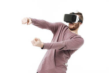 Young man in virtual reality glasses playing car simulator on white background. Portrait of boy using visual reality glasses isolated