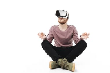 Young man sitting in studio and meditating while using virtual reality glasses isolated. Smiling boy playing with visual reality glasses on white background
