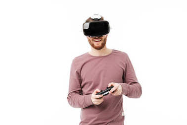 Young smiling man using virtual reality glasses and playing video game on white background. Cheerful boy with joystick in hands wearing visual reality glasses isolated