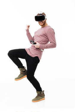 Young man standing in virtual reality glasses with joystick in hand and showing