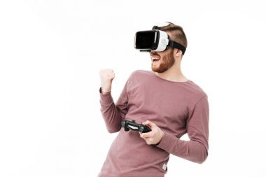 Portrait of young man standing in virtual reality glasses with joystick in hand and showing