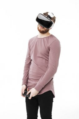 Portrait of young thoughtful man standing in studio with joystick in hands and using virtual reality glasses on white background. Cool boy playing with visual reality glasses isolated