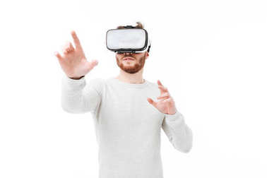 Portrait of young man in studio using virtual reality glasses on white background. Cool boy playing with visual reality glasses isolated