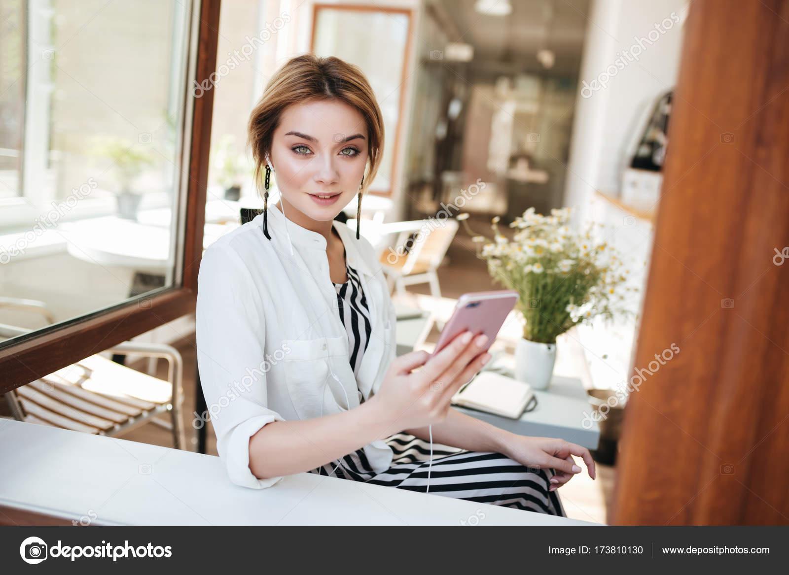 Portrait De Jeune Fille Dans Les écouteurs Assis Au Café à La