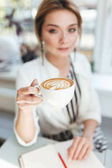 Portrait of young pretty girl with blond hair sitting in restaurant with notebook on table and drinking coffee. Close up woman hand holding cup of cappuccino in coffee shop