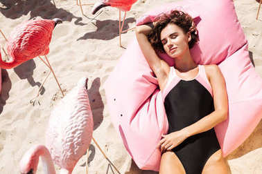 Young girl in swimsuit lying and sunbathing on big pink pillow next to flamingos on beach. Portrait of beautiful girl dreamily closing her eyes while spending time on beach