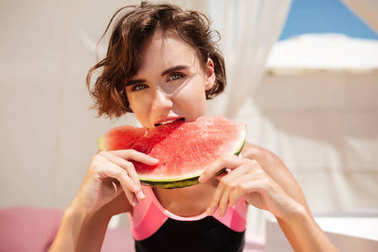 Portrait of beautiful girl in trendy swimsuit sitting in beach tent and dreamily looking in camera while eating watermelon. Young lady sitting with watermelon slice while spending time on beach