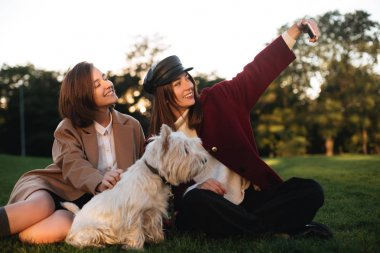 Portrait of two young smiling ladies sitting on grass and taking selfie on cellphone while spending time with their small cute dog in park