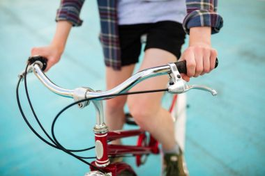 Close up photo of young man body riding red bicycle in park. Photo of red classic bicycle on basketball court