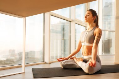 Young  lady in sporty top and leggings sitting in lotus pose and meditating on yoga mat at home with big beautiful windows on background