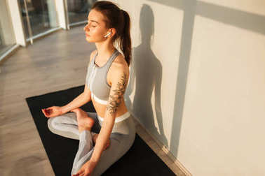 Portrait of lady in sporty top and leggings sitting in lotus pose and meditating on yoga mat while listening music in earphones at home isolated