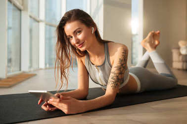 Portrait of beautiful lady in sporty top and leggings lying on yoga mat and happily looking in camera with laptop in hands at home with big windows on background