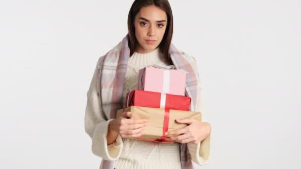 Krásná dívka s útulné kostkované na ramenou drží dárkové krabice v rukou šťastně dívá do kamery izolované