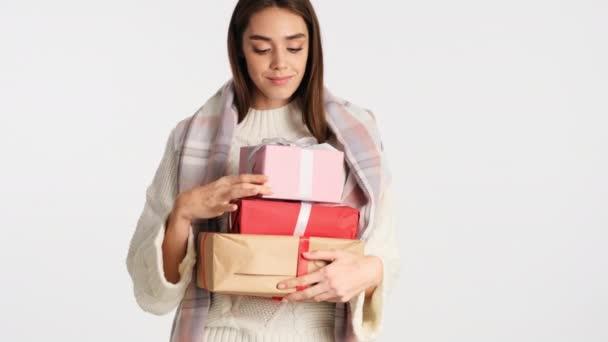 Krásná dívka s útulné kostkované na ramenou třesoucí dárkové krabice a šťastně se snaží hádat, co je tam přes bílé pozadí