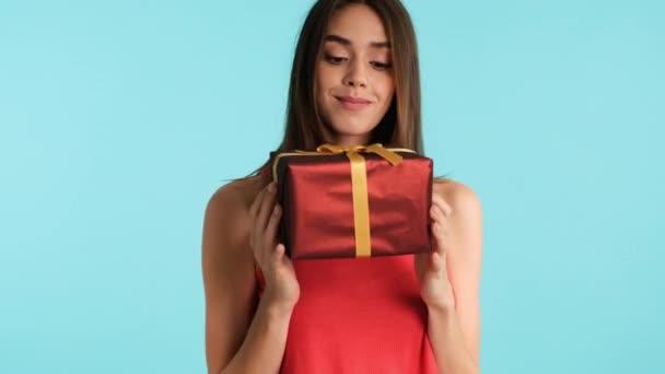 Pěkně ležérní dívka zasněně třesoucí dárkové krabice a snaží se hádat, co je tam přes barevné pozadí
