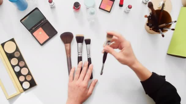 Top view shot of close up beauty blogger showing different brushes in make-up tutorial video