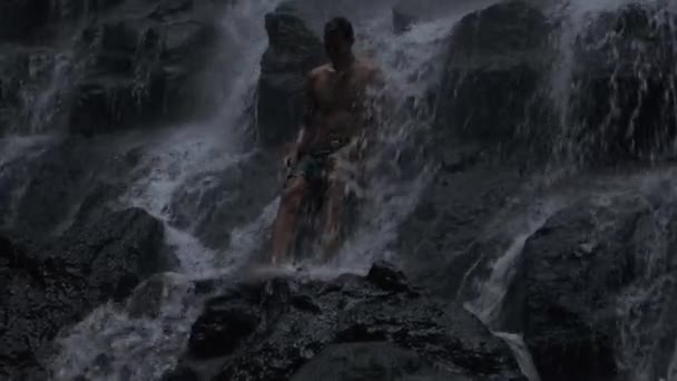 Tracking shot of  young handsome man standing on stone under waterfall on tropical island at dusk