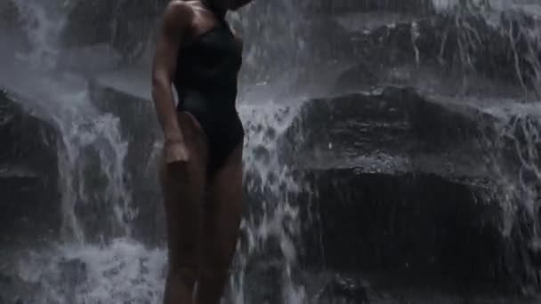 Tracking shot of gorgeous sexy girl in swimsuit posing on amazing tropical waterfall at dusk