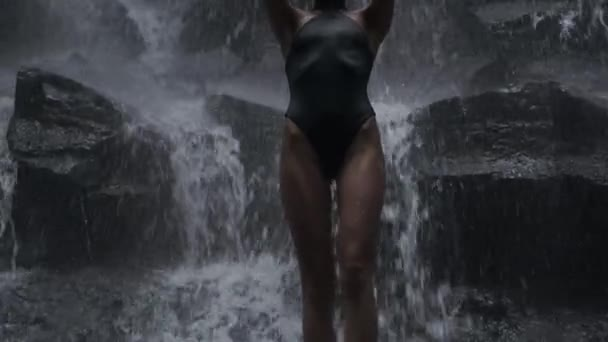Tracking shot of gorgeous sexy girl in swimsuit sensually posing on waterfall rock at dusk