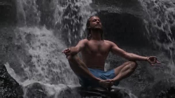 Young handsome man meditating at beautiful waterfall on tropical island at dusk
