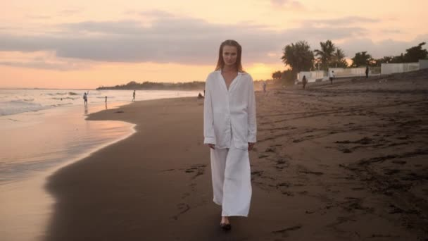 Tracking shot of stylish girl dreamily walking by the ocean during sunset on paradise island