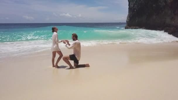 Tracking shot of handsome man standing on one knee and doing proposal to his pretty girlfriend on paradise island. Touching moment of couple getting engaged