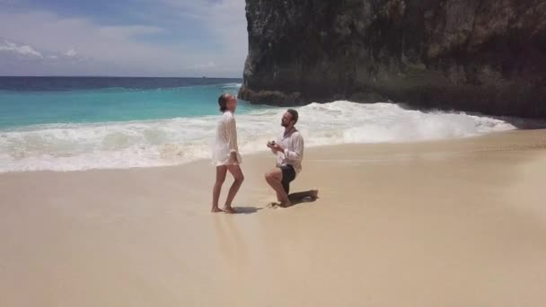 Young romantic man standing on one knee and doing proposal to his beautiful girlfriend on empty beach with blue ocean. Touching moment of couple getting engaged