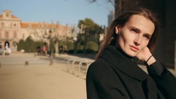 Tracking around shot of beautiful stylish fashion girl walking in sunny city park enjoying the sun. Gorgeous model with sculptural face wearing black coat standing in the sun