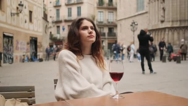Beautiful dreamy hispanic girl with glass of wine resting in outdoor cafe on city square