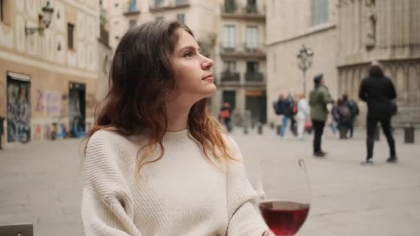 Tracking shot of pretty hispanic girl thoughtfully looking around resting in outdoor cafe with glass of wine