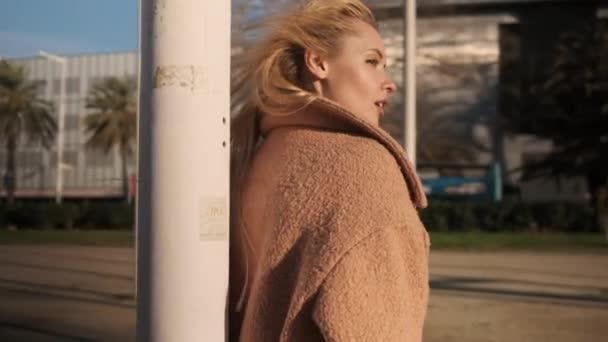 Nyomon követni egy gyönyörű szőke lányt, aki érzékien pózol a szabadban naplementekor.
