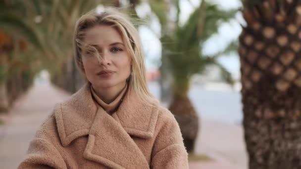 Csinos szőke lány szeles hajjal álmodozva néz a kamerába a város utcáján