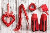 Fotografie Rote Schuhe schlagen Herz-Handschellen auf einem hölzernen Hintergrund