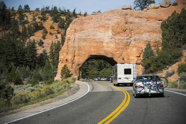car driving the Bryce Canyon road, amazing landscape of red rocks and evergreen trees