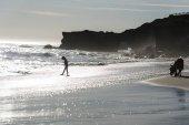 Fényképek Sziluettjét gyermek séta a homokos tengerpart naplemente alatt