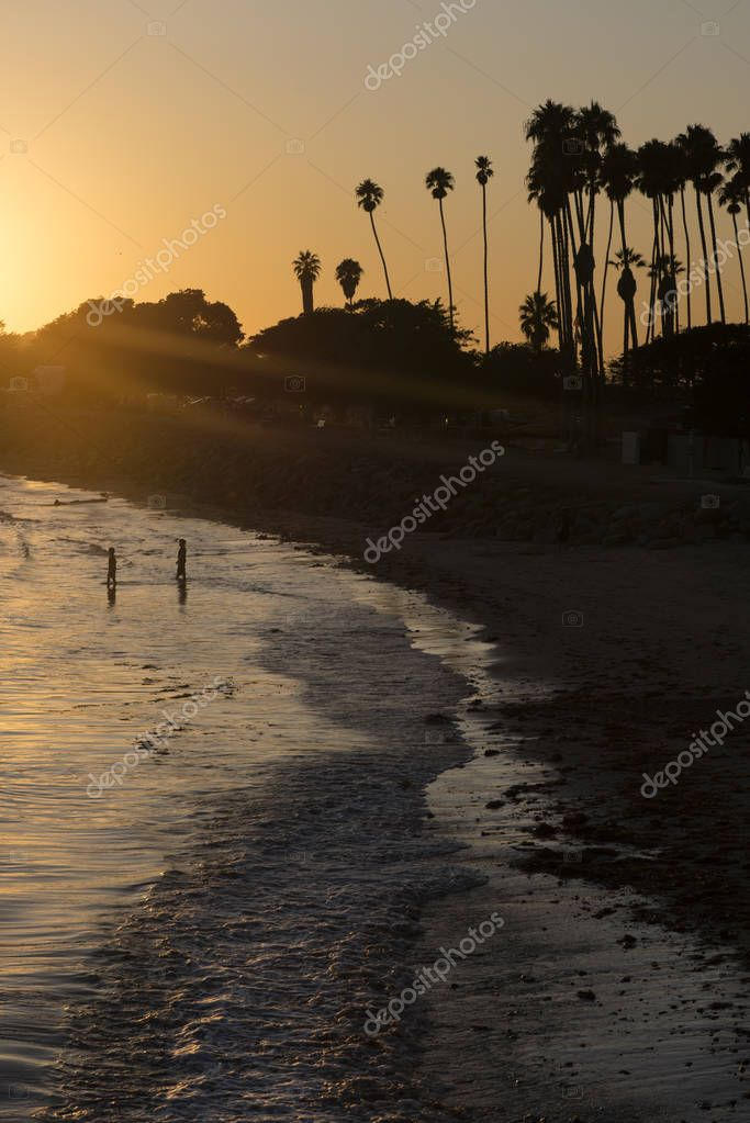 People on sandy beach during sunset