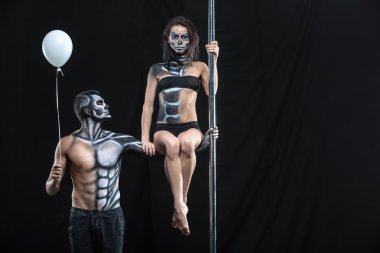 Couple of dancers with body-art and balloon