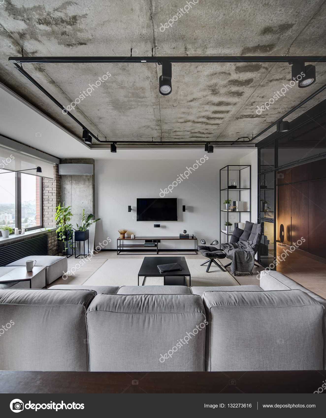 Loft Style Sitting Room With White, Brick And Concrete Walls. There Is Sofa,  Tables, Chair, Armchair, Shelves, Speakers, TV And Rack Under It, Lamps.