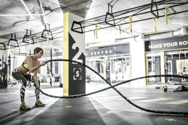 Girl does exercise with fitness rope in gym