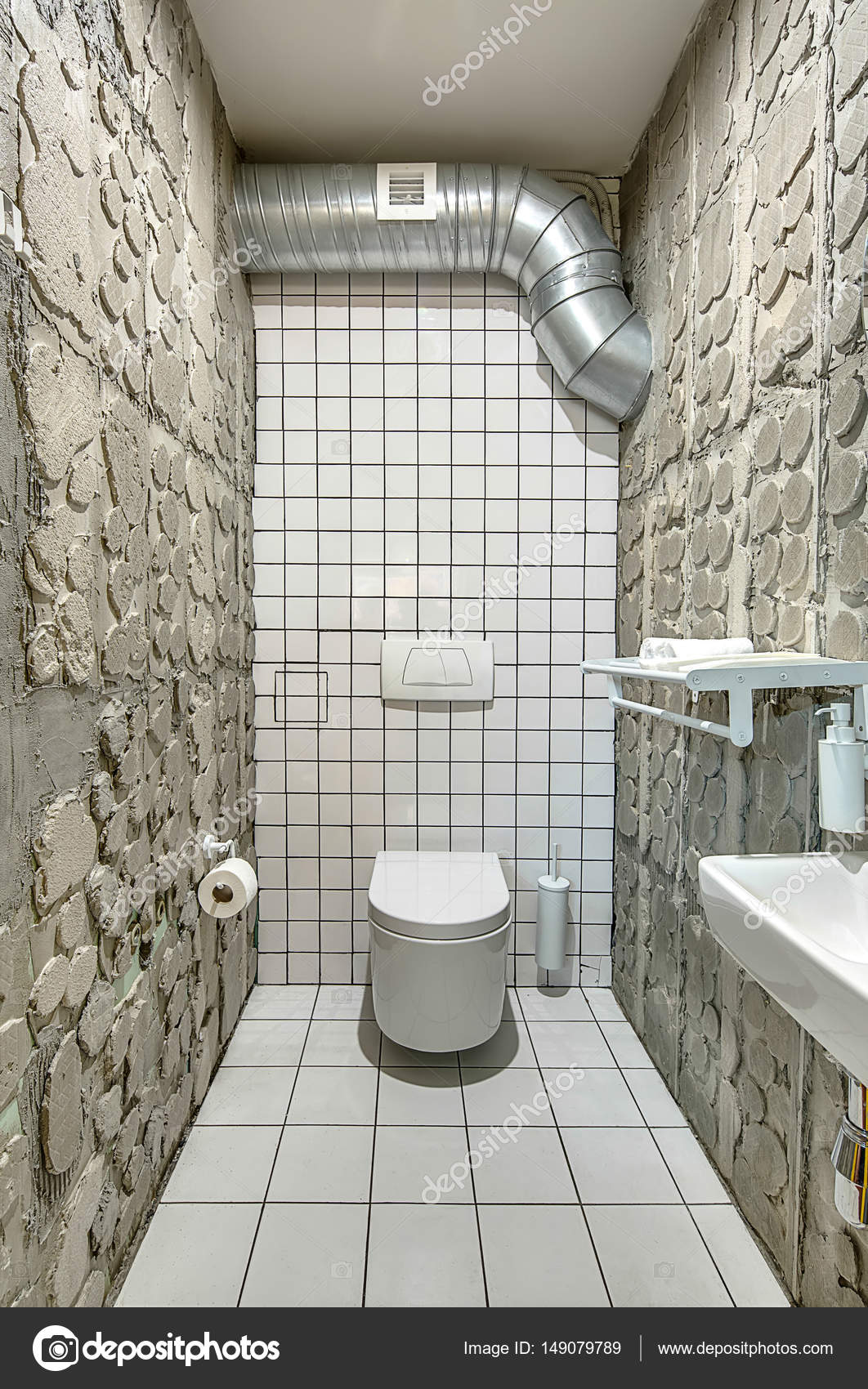 Restroom In A Cafe In A Loft Style With Tiled White Walls And Concrete  Walls. There Is A White Toilet, Sink, Shelf With Towels, Mirror, Paper  Holder, ...