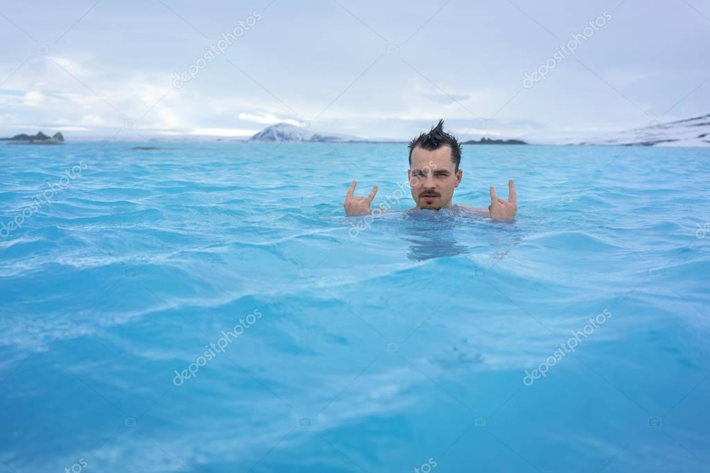 Guy relaxing in geothermal pool outdoors