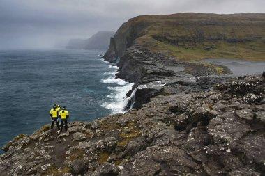 Guys on rocky seashore