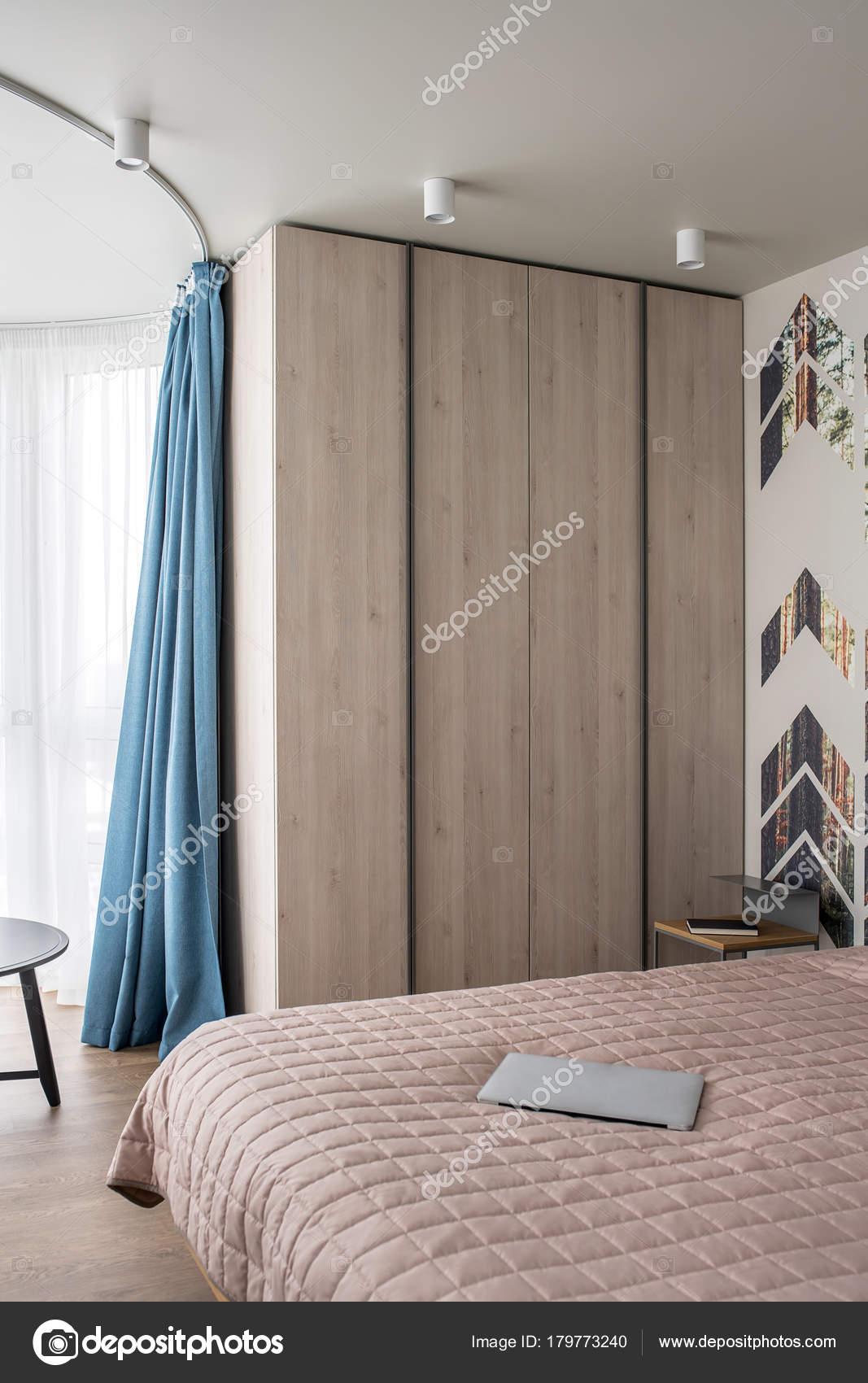 Gibt Es Ein Bett Mit Einer Tagesdecke Und Ein Laptop, Nachttisch Mit Buch,  Hölzerne Schrank, Dunklen Runden Tisch Gesims Mit Einem Blauen Vorhang.