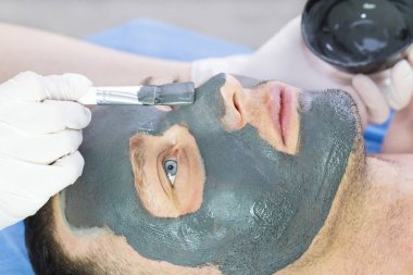 A man does the procedure cleaning his face with a clay mask in the beauty salon