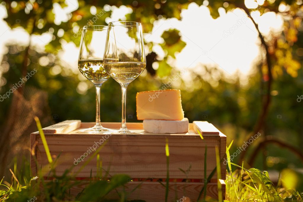 Two glasses of white wine with cheese on wooden box