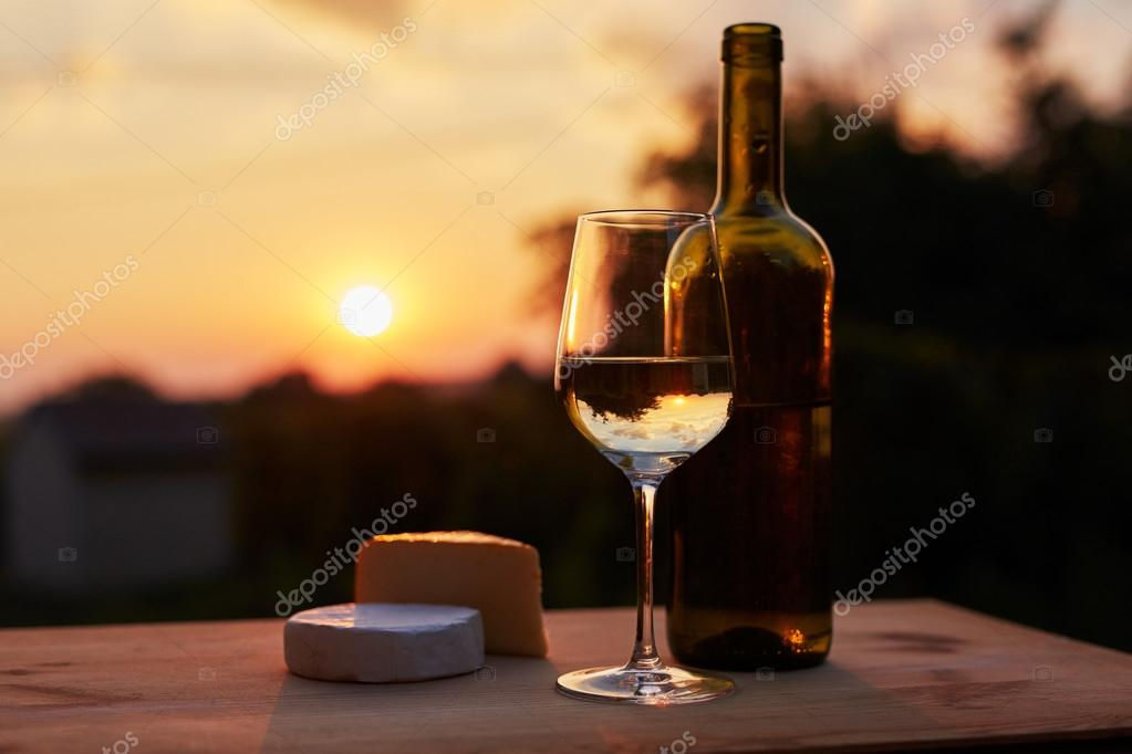 Low key image, glass of white wine with bottle